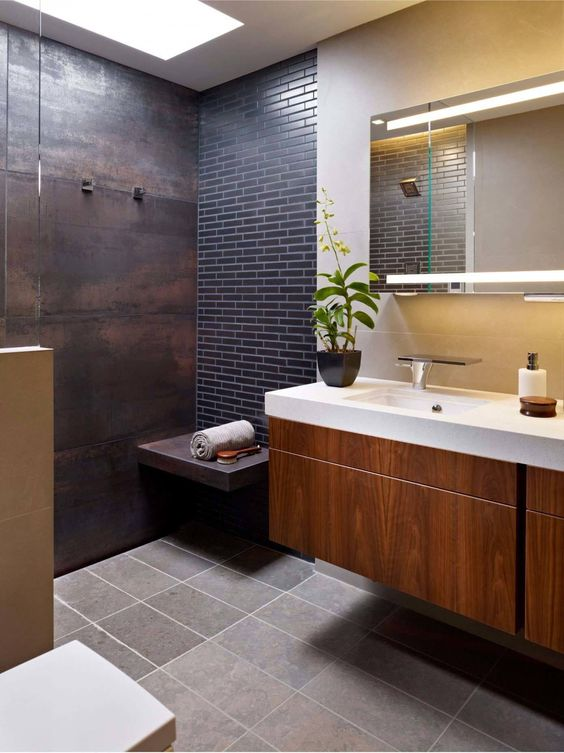 a shower space done with an aged metal wall and a navy skinny tile accent wall plus a floating bench of metal