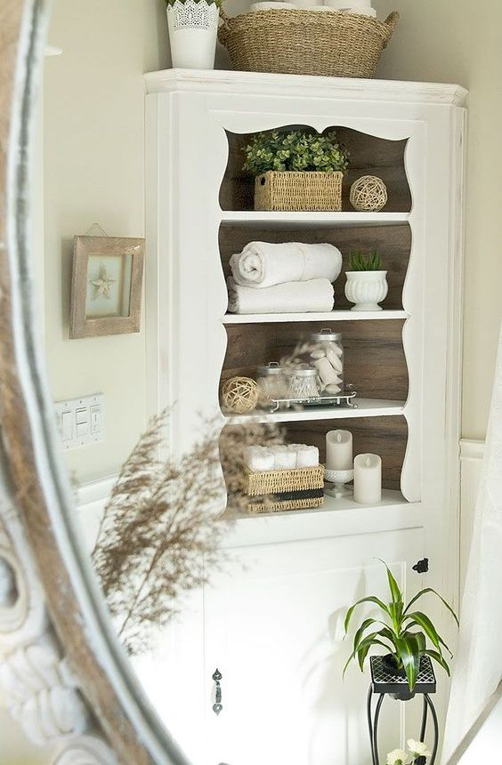 an elegant corner cabinet in white will add a vintage touch to your bathroom and give enough storage space