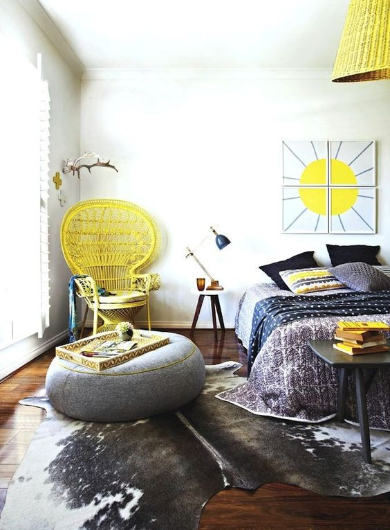 bright yellow touches including a peacock chair in the corner make this grey boho bedroom bold and sunshine-filled