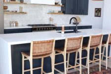 23 leather stools with wooden framing match the pendant lamps and refresh the monochromatic kitchen