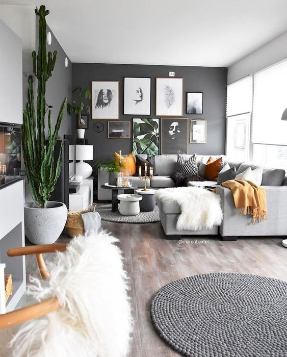 a black statement wall with a gallery wall is a cool and chic focal point for an open layout