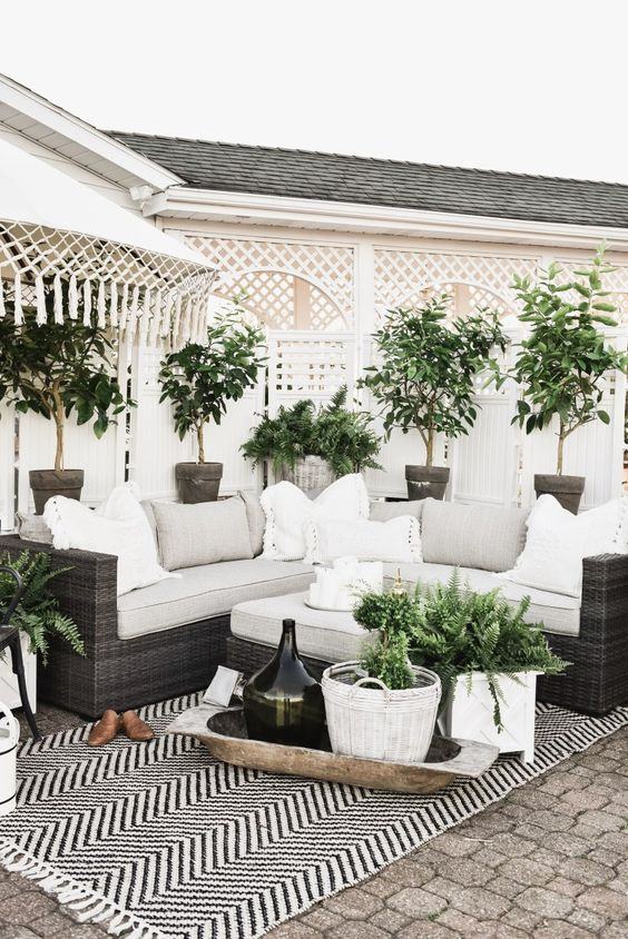 a chic farmhouse patio with potted greenery, a chevron rug, neutral pillows for a polishing touch