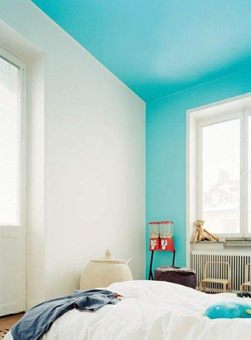a simple bedroom spruced up with a turquoise ceiling that comes down to the walls for a brighter touch