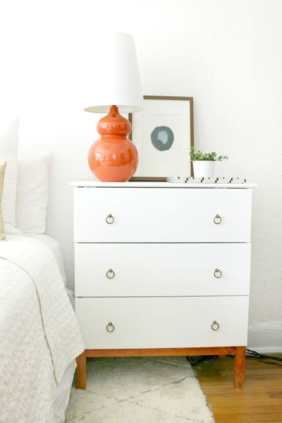 an IKEA Tarva dresser hack with white paint, stained legs and ring pulls provides much storage space