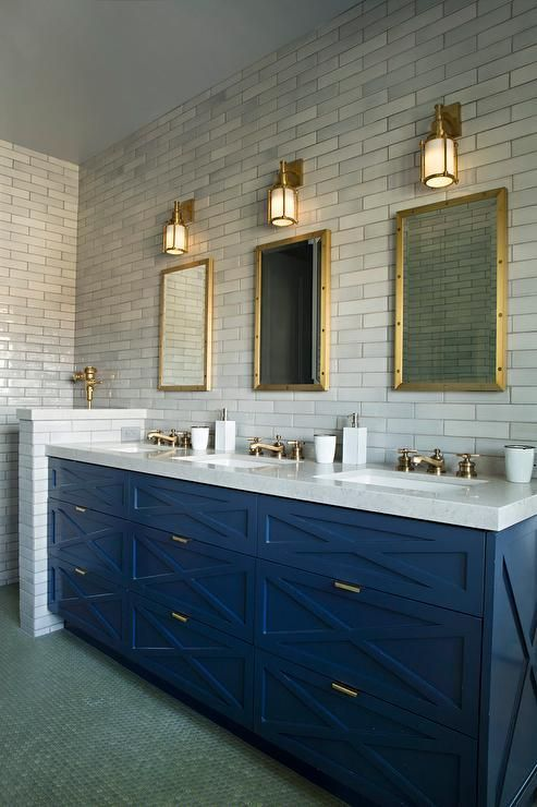 an art deco bathroom with marble skinny tiles, a bright blue vanity and brass touches here and there