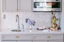 24 vintage grey kitchen cabinets and marble skinny tiles done in a chevron pattern for more eye-catchiness