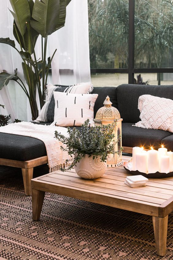 a chic patio decorated with contrasting blankets and pillows, candle lanterns and potted greenery