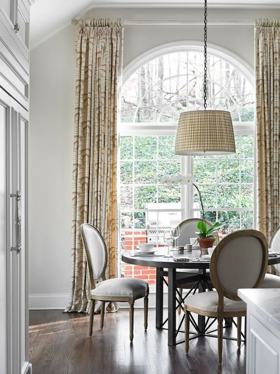 a formal meets farmhouse dining space with a large arched window that brings light inside