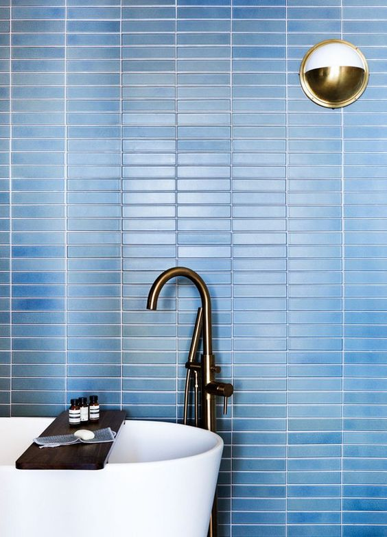refresh your contemporary bathroom with laconic blue skinny tiles on the wall accented with white grout