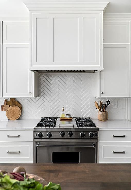 white skinny tiles clad in a herringbone pattern match the cabinets and add pattern interest to the kitchen