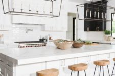 25 wooden kitchen stools with black metal legs add texture to the space and warm up the white interior a bit