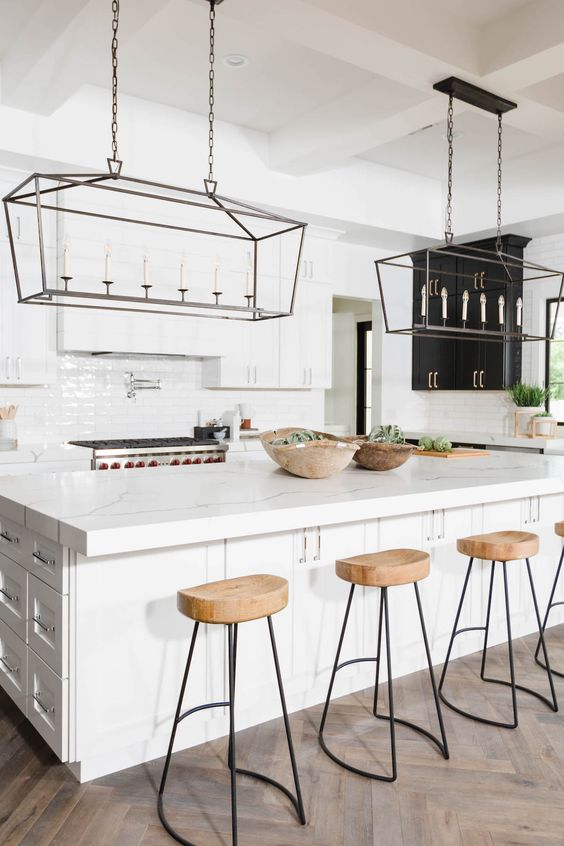 wooden kitchen stools with black metal legs add texture to the space and warm up the white interior a bit