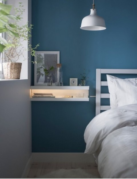IKEA Mosslanda ledges turned into a floating nightstand with lights, which is ideal for a small bedroom
