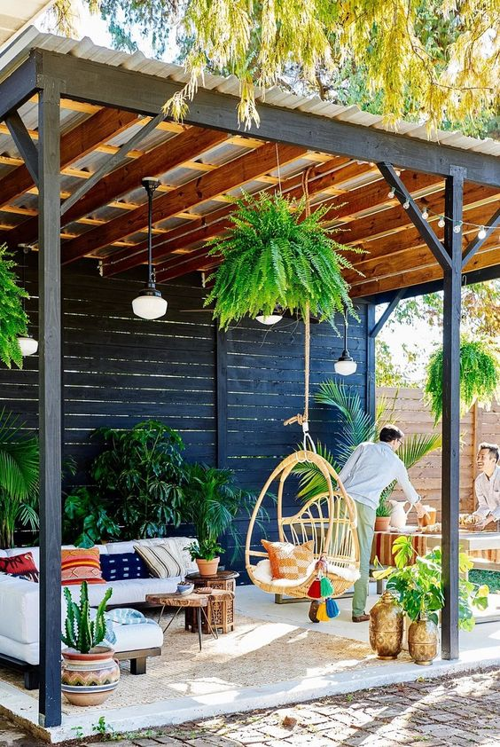 a bright patio with potted greenery, colorful pillows, a hanging rattan chair and pendant lamps