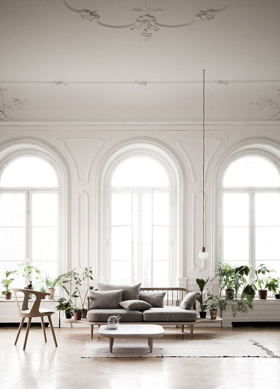 a contemporary living room featuring lots of arched windows with much light and coziness