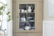 26 a neutral fully closed corner cabinet with some glass to display tableware in your dining space