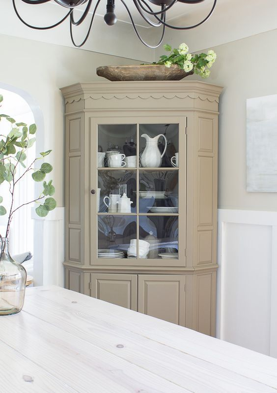 a neutral fully closed corner cabinet with some glass to display tableware in your dining space