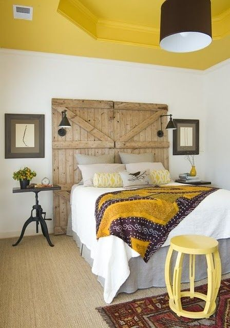 a rustic meets modern bedroom with a bright yellow ceiling and a matching blanket and a side table