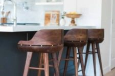26 very eye-catchy dark stained wooden stools contrast the black and white kitchen island and look rich