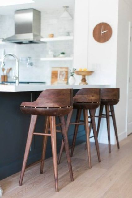 very eye catchy dark stained wooden stools contrast the black and white kitchen island and look rich