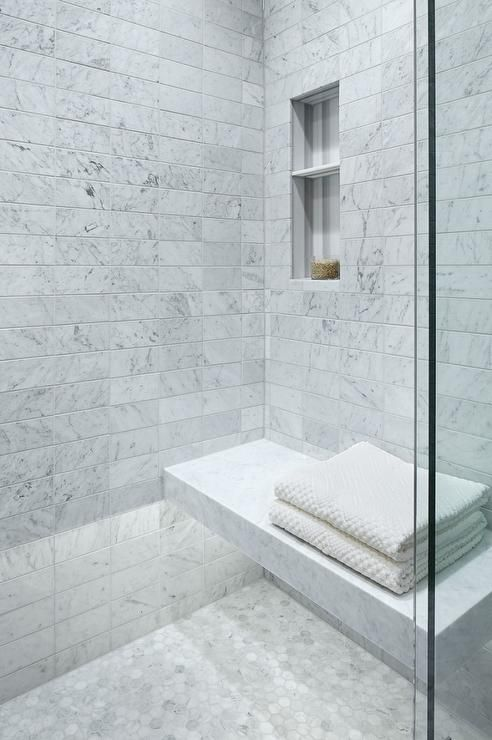 a Carrara marble shower space with a floating bench and nches in the wall is a chic and bright idea
