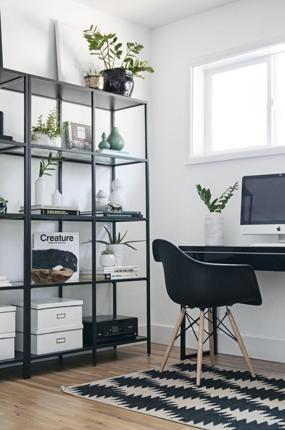 a Nordic black and white home office with a printed rug, a black shelving unit and desk plus a chair
