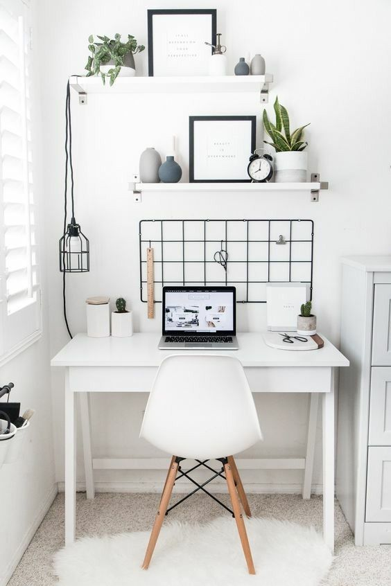 a Nordic home office nook done in white and accented with a black grid on the wall, a pendant lamp and chair elements