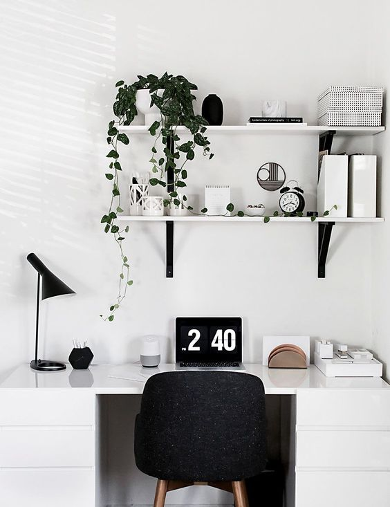 a Scandinavian home office nook with a white desk, a black chair, lamp and some wall-mounted shelves
