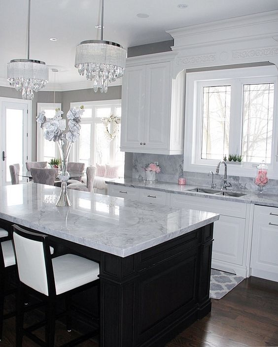 a black kitchen island and white cabients are covered with the same neutral stone countertops for a cohesive look