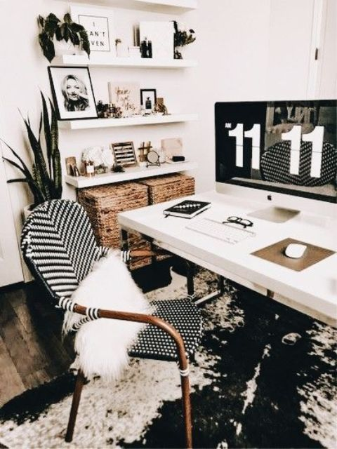 a boho black and white home office with an abstract rug, a white desk and shelves, a rattan chair and baskets for storage