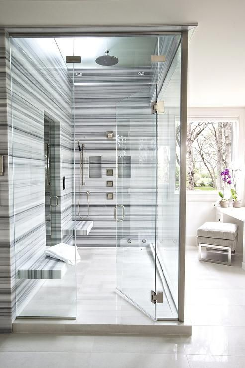 a bold modern shower space done with blue striped marble and two floating benches that don't take much space