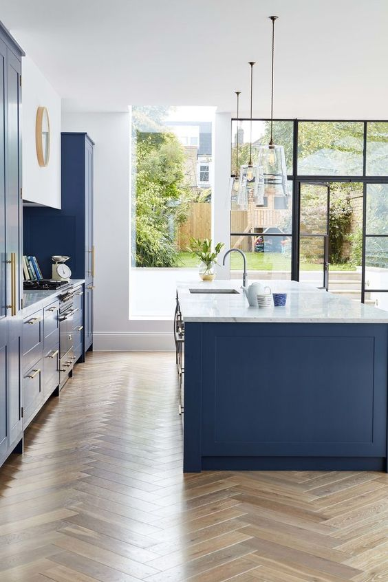 a bright and fresh blue kitchen with white stone countertops and brass hardware looks very chic