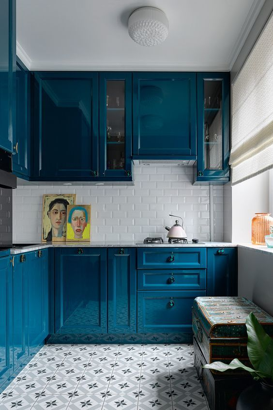 a bright blue kitchen with a white stone countertop and a white subway tile backsplash for a highly contrasting look