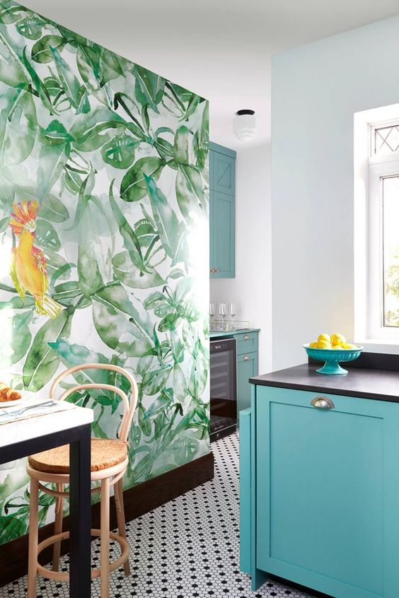 a bright tropical kitchen with blue cabinets, a mosaic tile wall, a tropical leaf statement wall, rattan stools
