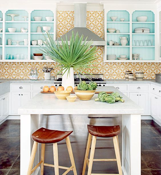 a bright tropical kitchen with yellow mosaic tiles, blue cabinets, tropical plants and leather and wood stools