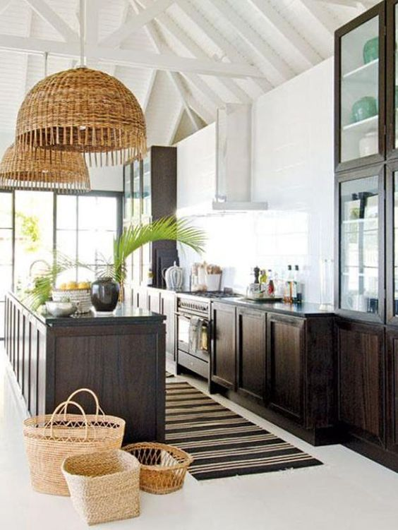 a chic tropical kitchen with dark stained cabinets, baskets, wicker lampshades, tropical plants and a striped rug