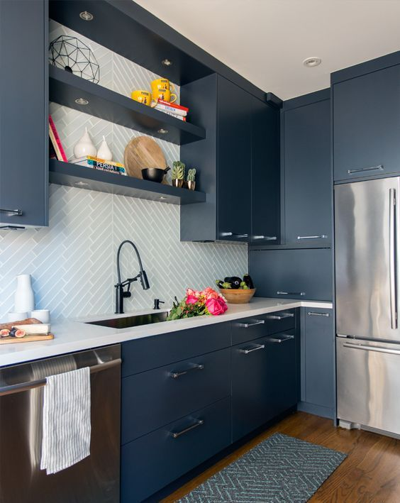 a contemporary blue kitchen with white countertops and a white tile backsplash clad with a pattern