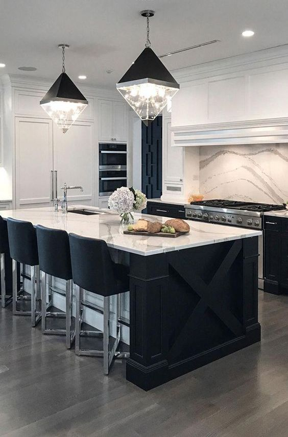 a contemporary kitchen with black cabinets, white stone countertops and a matching backsplash plus catchy lamps