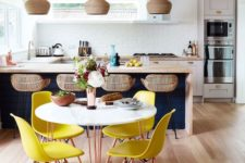 a cool tropical kitchen with a navy kitchen island plus white cabinets, rattan stools and wicker lamps, bright yellow chairs and a round table