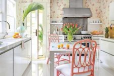 a creative tropical kitchen with flamingo wallpaper, sleek white cabinets, pink rattan chairs, tropical plants