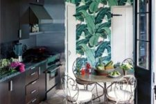 a dark kitchen with bright tropical leaf wallpaper, forged furniture and black countertops for a bold look