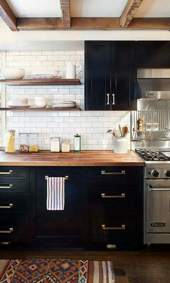 a farmhouse kitchen with black cabinets, neutral butcherblock countertops and brass hardware