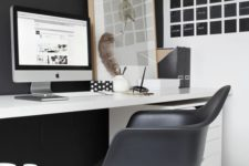 a laconic Nordic home office with a black statement wall and chair, a black noteboard, a white desk and a relaxed artwork