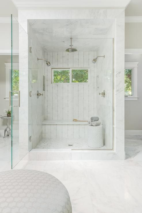 a mini marble shower space with windows and a built-in bench plus a side table with towels