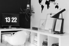 a minimalist black and white home office with a black statement wall, a map on the wall, a comfortable storage unit and a white chair