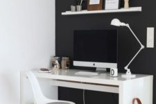 a minimalist black and white home office with a black statement wall, white furniture and some art