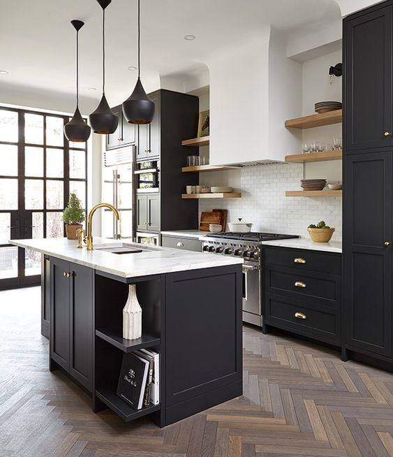 a modern farmhouse kitchen with black cabinets and white stone countertops plus brass hardware