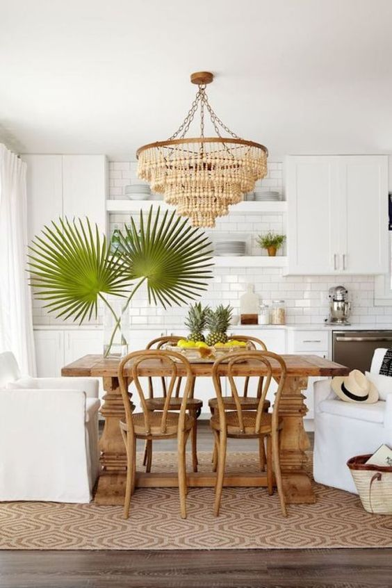 a modern kitchen in white, with a subway tile backsplash, a wooden bead chandelier, a wooden dining table and rattan chairs