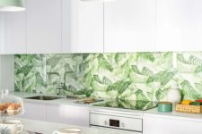 a modern tropical kitchen with sleek white cabinets, a tropical leaf print backsplash, green pendant lamps and wooden chairs