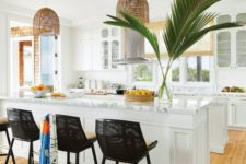 a modern tropical kitchen with white cabinets, marble countertops, wicker lampshades, black chairs and wicker shades